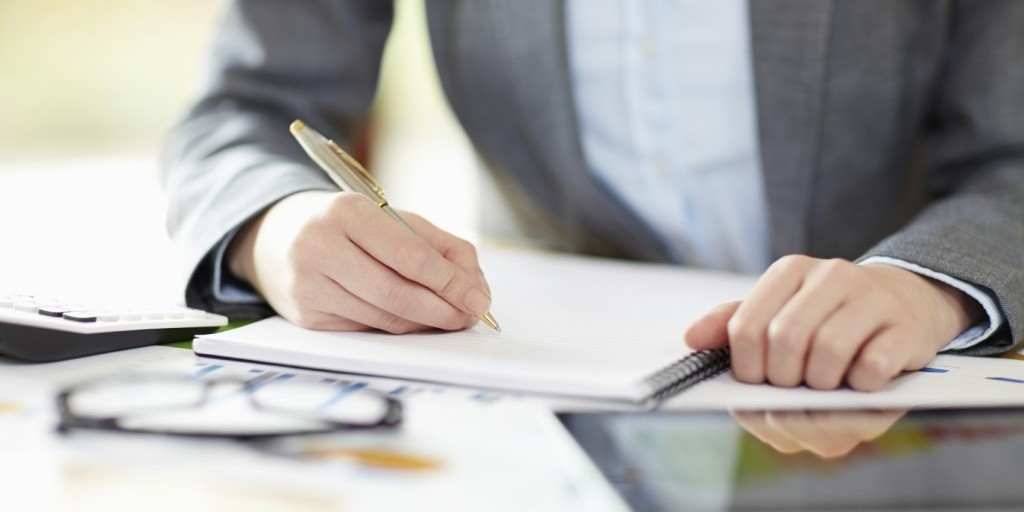 Midsection image of a businesswoman writing in note pad at desk. She is calculating financial performance. Female executive is with documents and digital tablet in office. Focus is on her hands.