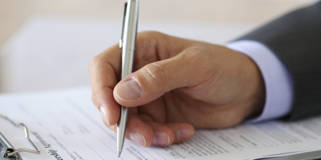 Hand of businessman in suit filling and signing with silver pen partnership agreement form clipped to pad closeup. Business success, contract, paperwork or lawyer concept